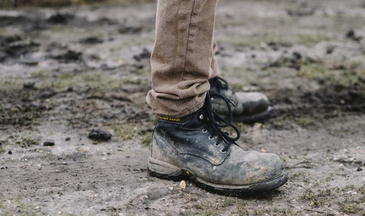 An image of a person wearing a pair of muddy walking boots, on a dirt path.