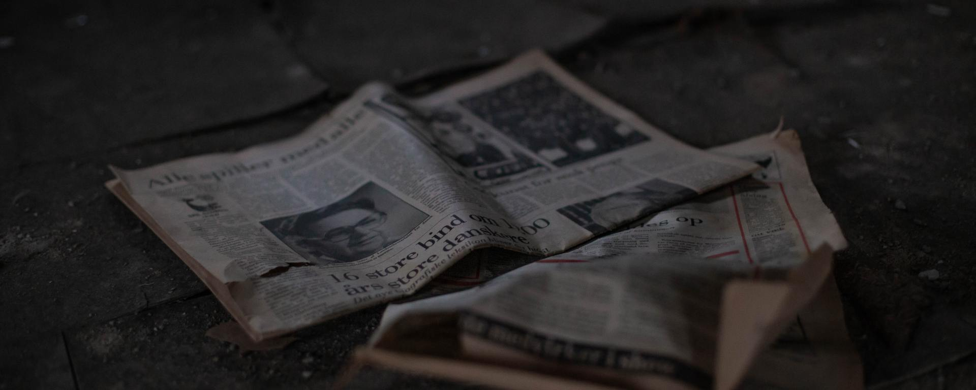 An image of a crumpled newspaper on the ground.