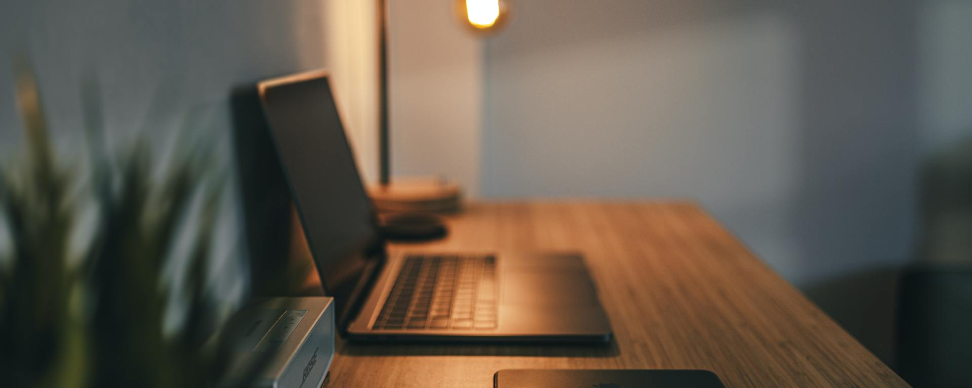 An image of a laptop and phone on a wooden desk with a lamp in the background.