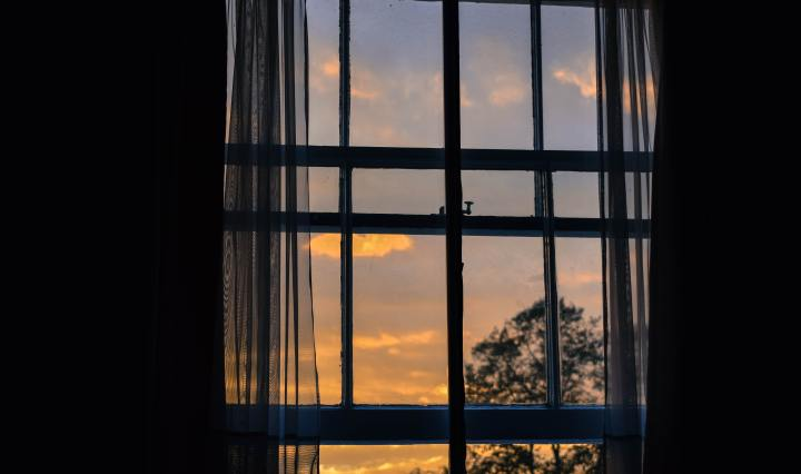 An image of a sunrise through a window, with trees in the distance.