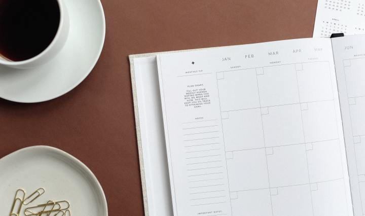 An image of a diary calendar on a surface, with a cup of black coffee and small dish of paperclips.
