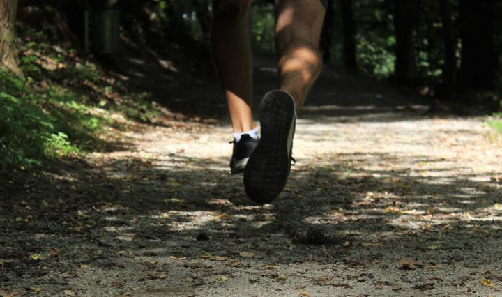 An image of legs and shoes, running along a woodland trail.